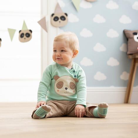 Kind mit Panda Pullover sitzt auf dem Boden